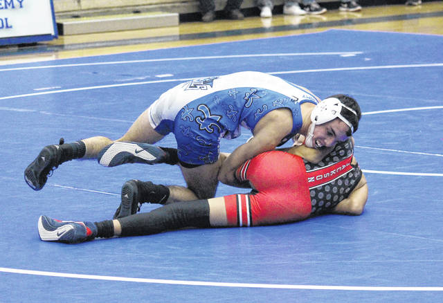 Gallia Academy senior Caleb Greenlee rolls his opponent onto his back during, during a 113-pound match on Wednesday in Centenary, Ohio.