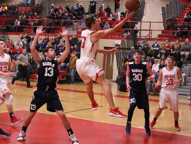 Wahama senior Skyler Estep releases a layup attempt between Hannan defenders Dalton Coleman (13) and Matthew Qualls (30) during the first half of Friday night's boys basketball contest in Mason, W.Va. (Bryan Walters|OVP Sports)