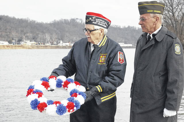 World War II veteran Milford Mowrey, left, is pictured as he prepares to toss a wreath into the Ohio River Thursday, as part of a ceremony honoring those who lost their lives or were injured at Pearl Harbor on Dec. 7, 1941. Also shown is veteran John Hood. The remembrance was held at the Mason levee, with the Stewart-Johnson V.F.W. Post 9926 of Mason, Smith-Capehart American Legion Post 140 of New Haven, and Drew-Webster American Legion Post 39 of Pomeroy participating.