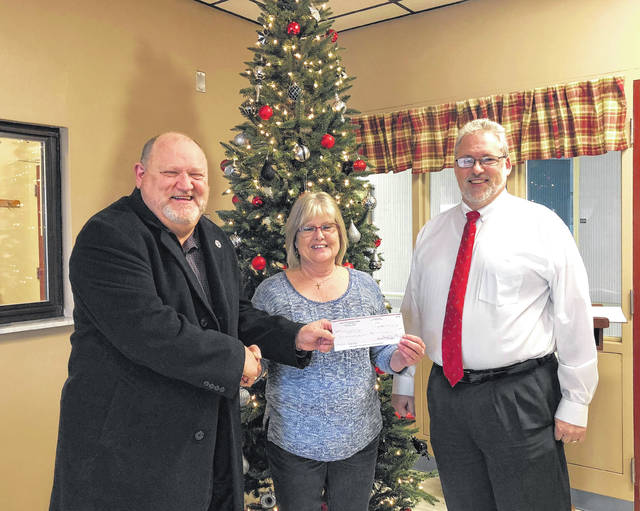 """Community Christmas Cantata donations of $525 went to Lakin Hospital's, """"Operation Santa Claus."""" Pictured are Larry Jones from the cantata, Darlene Ash of Lakin and John Machir a choir member."""