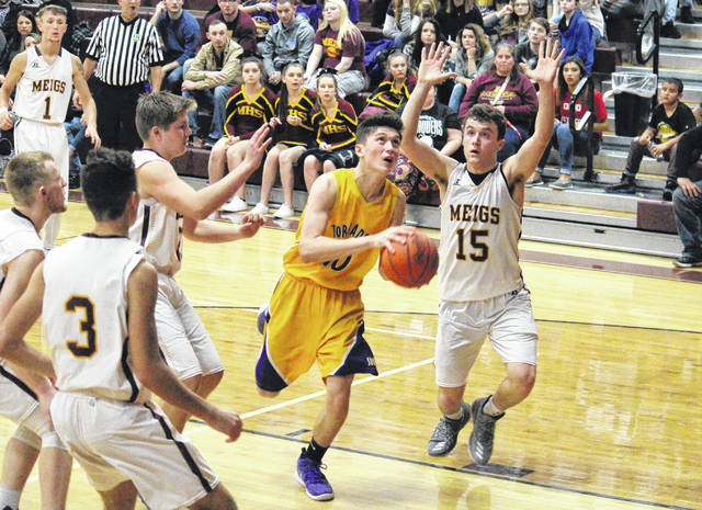 Southern junior Austin Baker (center) goes in for a layup in front of MHS junior Zach Bartrum (15) during the the Tornadoes' 76-68 victory on Saturday in Rocksprings, Ohio.