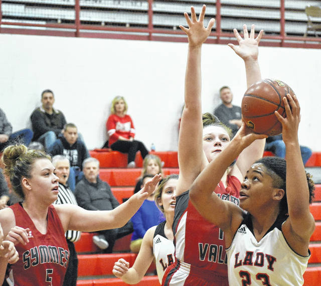 Point Pleasant junior Lanea Cochran (23) attempts a shot over two Symmes Valley defenders during the first half of the Lady Knights' 55-42 loss on Saturday at Point Pleasant High School.