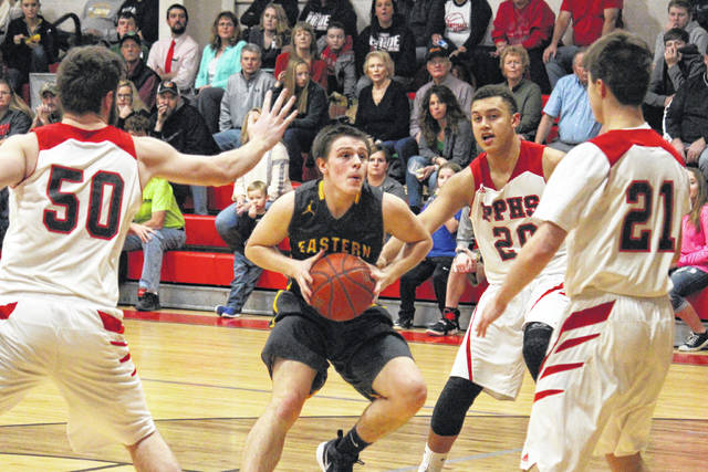 Eastern junior Isaiah Fish (center) drives between Big Blacks Trace Derenberger (50), Malik Butler (20) and Kyle Martin (21), during the first half of the Eagles' 53-45 victory on Tuesday in Point Pleasant, W.Va.