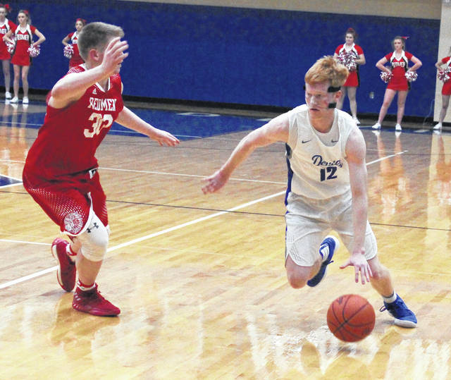 Gallia Academy senior Kaden Thomas (12) dribbles past a Rock Hill defender during the second half of Tuesday night's OVC boys basketball contest in Centenary, Ohio.