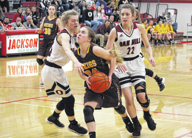 Meigs junior Madison Fields (center) drives in between Lady Oaks Peyton Miller (left) and Kasey Riley (22), during the Division III sectional semifinal on Wednesday in Jackson, Ohio.