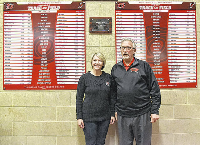 University of Rio Grande/Rio Grande Community College President Dr. Michelle Johnston and Rio Grande Athletic Hall of Famer Bernie Tilley pose in front of the school's new track & field record boards during a recent dedication ceremony at the Lyne Center. The boards were dedicated in honor of Tilley and his late sons, Kyle and Josh.