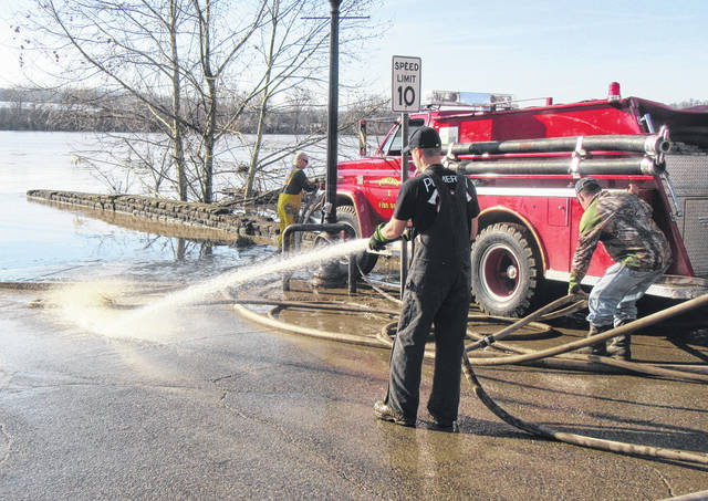 Volunteer firefighters from the Pomeroy Volunteer Fire Department worked to clear the downtown area on Tuesday, hosing off the parking lot and streets, and clearing roadways.
