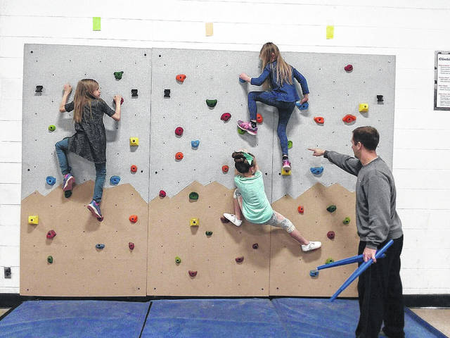 Leon elementary students climbing the newly installed climbing wall in their school's gymnasium.