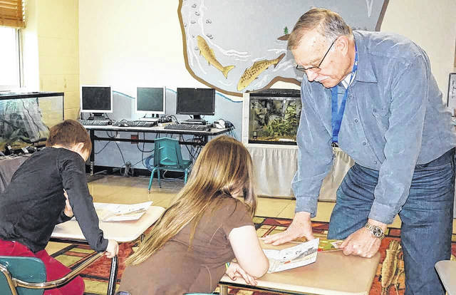 Pharmacist Dan Riggs is pictured providing reading assistance to a small group of first graders at New Haven Elementary as part of the Tiger Men program. The dozen volunteers range in age from 18 to the early 70s, and include a high school senior, college nursing student, pastors, an engineer and more. The Tiger Men provide students with both academic assistance and social interaction.