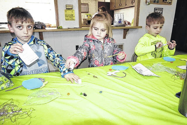 Siblings Carson, Paisley and Blake Roach, from left, children of Stephen and Amber Roach, are pictured as they begin making their crafts at the Letart community Easter egg hunt.