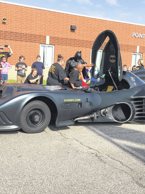 Lewis Bryant getting into the Batmobile with help from his mother and West Virginia Batman.