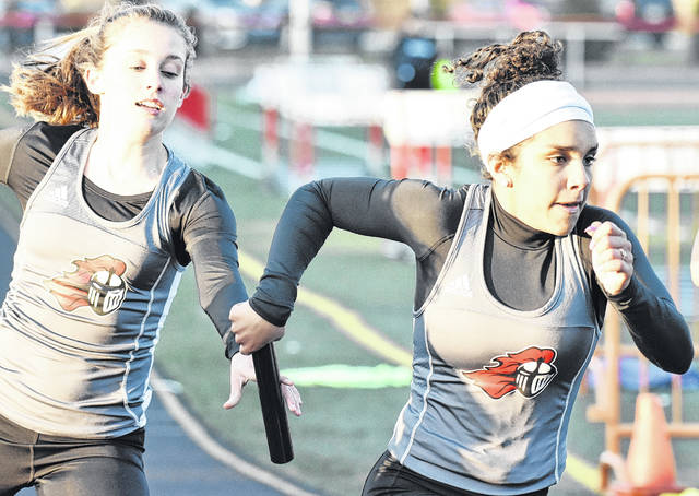 PPHS junior Sydnee Moore (right) takes the baton from teammate Allison Henderson during the 4x200-meter relay held at the Point Pleasant Open Meet on April 17 in Mason County.