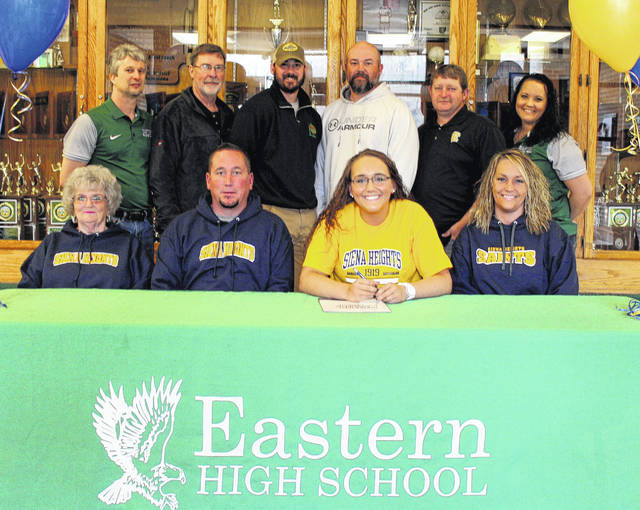 On Monday at Eastern High School, senior Elizabeth Collins signed her National Letter of Intent to join the Siena Heights women's basketball team next season. Sitting in the front row, from left, are Nancey Collins, John Collins, Elizabeth Collins and Melissa Collins. Standing in the back row are EHS assistant coach Jay Reynolds, former Lady Eagles assistant coach Tim Baum, Eastern head coach Jacob Parker, Lady Eagles assistant coach Brian Bowen, former EHS head coach John Burdette, and Eastern assistant coach Ashley Roush.