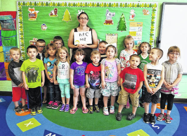 Leon Elementary preschool class with parent volunteer Rachel Payne holding the book they made for her.