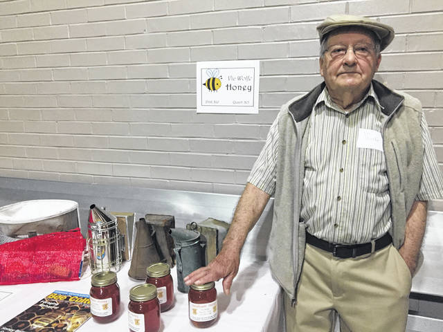 Vic Wolfe displays honey harvested from his hives.