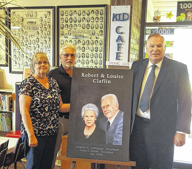 """A portrait of the late Robert and Louise Claflin was placed near the """"Kid Café"""" at the New Haven Library recently, which was funded through a Claflin Foundation grant. The grant money was used at all three county libraries to establish cafes to feed children free lunches and snacks throughout the summer, regardless of parents' incomes. Pictured, from left, are Pam Thompson, library director, Gary Fields, Claflin Foundation secretary, and Stephen Littlepage, Claflin Foundation president."""