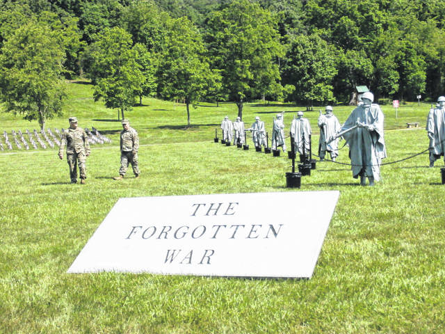 Soldiers with the West Virginia Army National Guard walk past replicas of their Korean War counterparts on Friday in Letart.