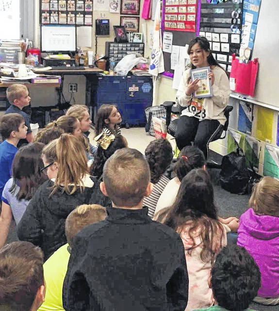 Olivia Li, intern for the International Programs and Services department, reads to students at Rio Grande Elementary. Li is the first international student to graduate from the Master of Education in Integrated Arts degree program.