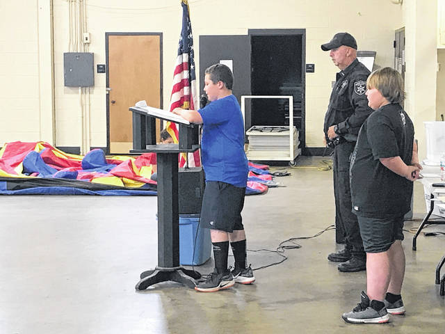 DARE essay winner Caleb Jones, pictured at the podium, reads his submission during the DARE graduation alongside fellow essay winner from Roosevelt Elementary Justin Saxon and DARE Program Coordinator Lt. Troy Stewart.