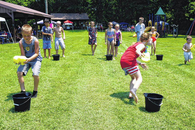Water games were popular at the Mason park during July 4 activities. Pictured are children as they race to fill the bucket with water, using wet sponges.