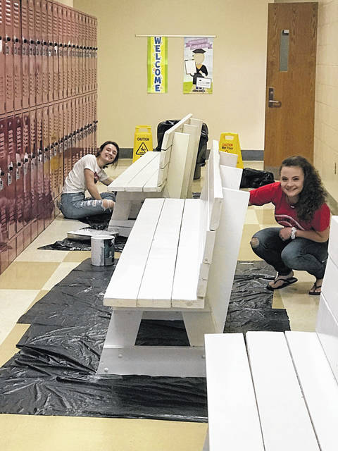 Students at Wahama High School are pictured as they paint benches to spruce up the interior of the facility.