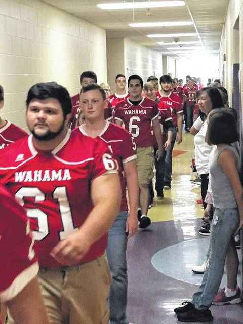 """The Wahama White Falcon football team, band, cheerleaders and mascot marched through the halls of New Haven Elementary School Friday morning to share their team spirit for that evening's football game. With the band playing """"Stand Up and Cheer,"""" the elementary students got to see what it might be like to take part in a high school organization, while the older students were able to represent themselves as role models for the younger set."""