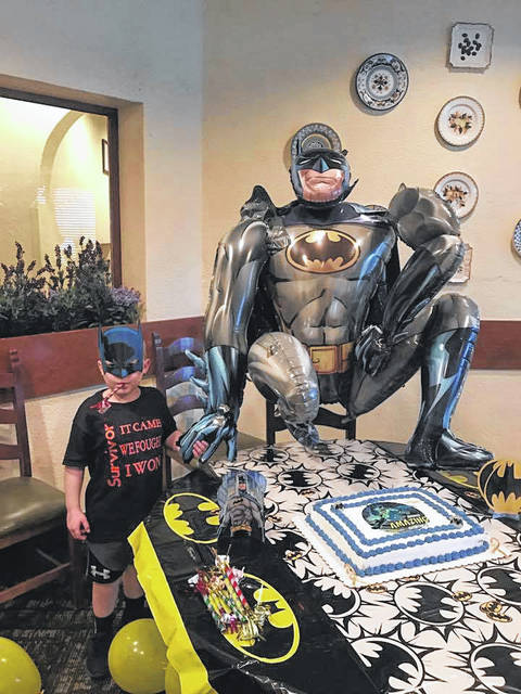 Holdyn Keefer, sporting a Batman mask, celebrating his end of chemotherapy treatment.