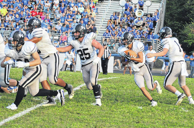 River Valley junior Jared Reese, second from right, takes a handoff during the first quarter of a Week 2 football contest against Gallia Academy at Memorial Field in Gallipolis, Ohio.