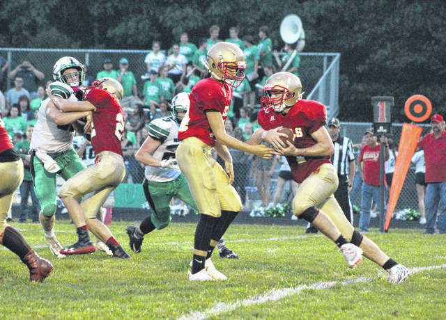 South Gallia junior running back Kyle Northup receives a handoff from quarterback Tristan Saber during the first half of Friday night's Week 2 TVC Hocking football contest against Waterford in Mercerville, Ohio.