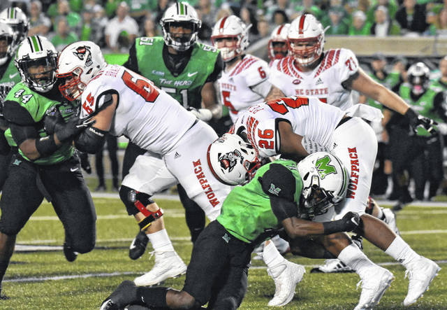 MU junior Jaylon McClain-Sapp stops North Carolina State freshman Trent Pennix (26) behind the line of scrimmage, during Marshall's 37-20 setback on Saturday at Joan C. Edwards Stadium in Huntington, W.Va.