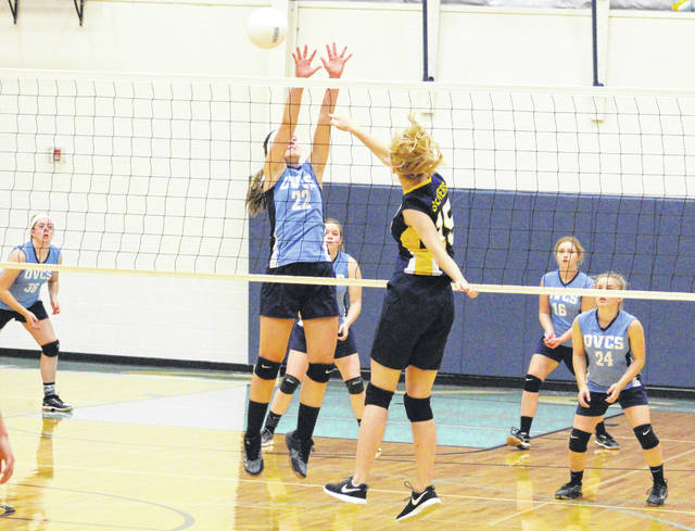 Ohio Valley Christian sophomore Laura Young (22) goes up for a block attempt during Game 3 of Tuesday night's non-conference volleyball match against Grace Christian in Gallipolis, Ohio.