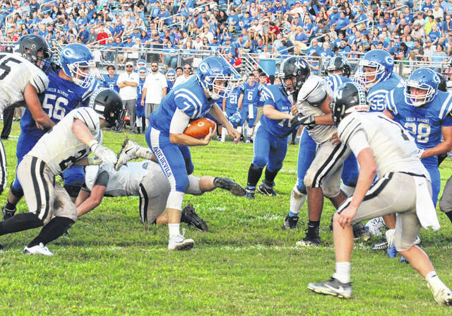 Gallia Academy senior quarterback Justin McClelland (7) crosses the goal line for a touchdown in between a handful of River Valley defenders during the first half of Saturday night's Week 2 football contest at Memorial Field in Gallipolis, Ohio.