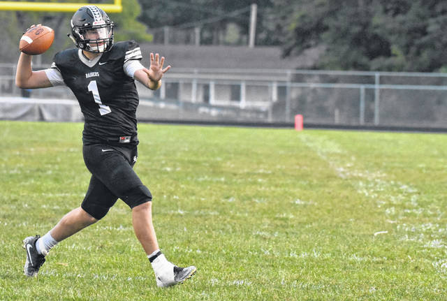 RVHS junior Jordan Burns attempts a pass during the first quarter of the Raiders 35-7 setback against Portsmouth on Friday night in Bidwell, Ohio.