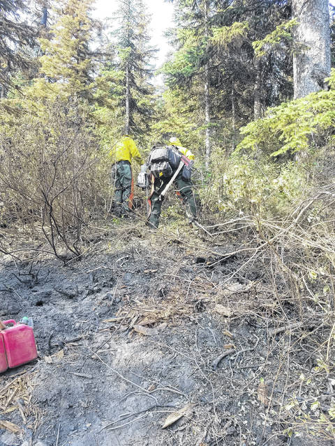Fire fighting crews cut brush to get hose laid to put out spot fires.