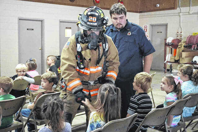 A fully suited firefighter walks among the kindergarten students from New Haven Elementary School this week to show them not to fear the fireman if a blaze occurs at their home. The demonstration was a part of Fire Prevention Week at the New Haven Fire Station.