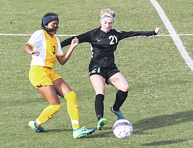Rio Grande's Payten Davis beats West Virginia University-Tech's Veronica Nobles to the ball during the first half of Thursday night's game at Evan E. Davis Field. Davis scored both of the RedStorm's goals, including the game-winner with 1:44 left to play, in a 2-1 win over the Golden Bears.