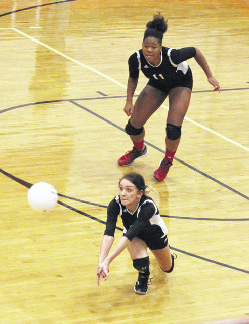 Point Pleasant senior Savanah Wroten dives for a bump attempt in front of classmate Lanea Cochran (11) during Game 1 of Monday night's non-conference volleyball contest against Teays Valley Christian in Point Pleasant, W.Va.