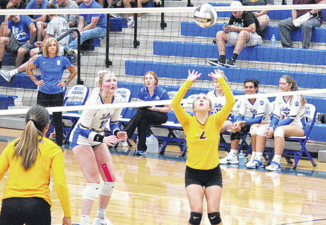 Meigs senior Madison Fields (2) sets the ball to teammate Marissa Noble (left), in front of GAHS senior Ashton Webb (11) and Blue Angels head coach Janice Rosier, during Gallia Academy's straight games win on Sept. 18 in Centenary, Ohio.