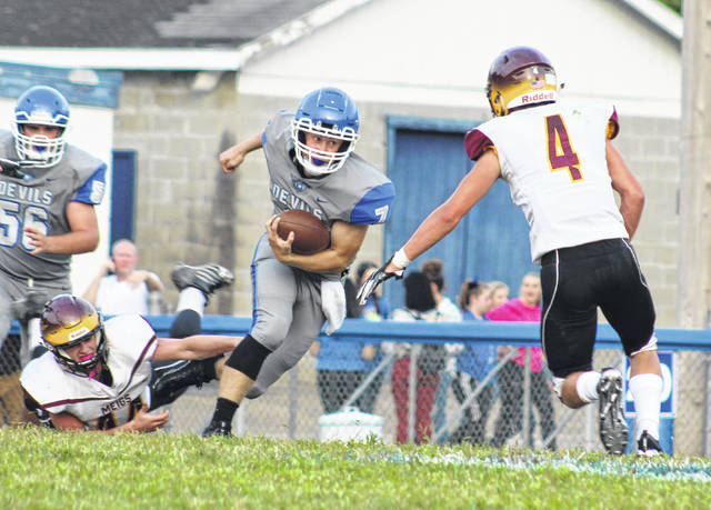 Gallia Academy senior quarterback Justin McClelland (7) breaks away from a tackle during the first half of an Aug. 24 football contest against Meigs at Memorial Field in Gallipolis, Ohio.