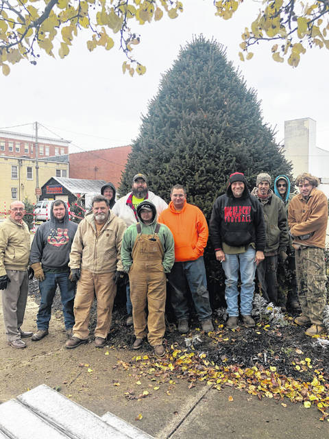 Mayor Brian Billings and Street Commissioner Randy Hall, along with employees with the city's street department, are pictured along with Point Pleasant's official Christmas tree in Gunn Park. Street department staff helped move the tree into its new home ahead of this Friday's lighting ceremony.