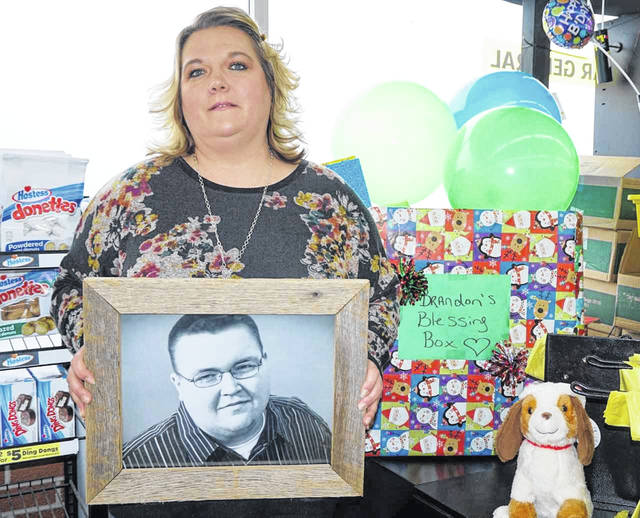 A toy drive in memory of Brandon Cundiff is now in its fifth year, with the toys going to patients on the cancer floor of Nationwide Children's Hospital in Columbus. Brandon passed away at the age of 18 from leukemia. His mother, Angel Darst, is shown with a photo of Brandon next to a collection box at Dollar General Store in New Haven.