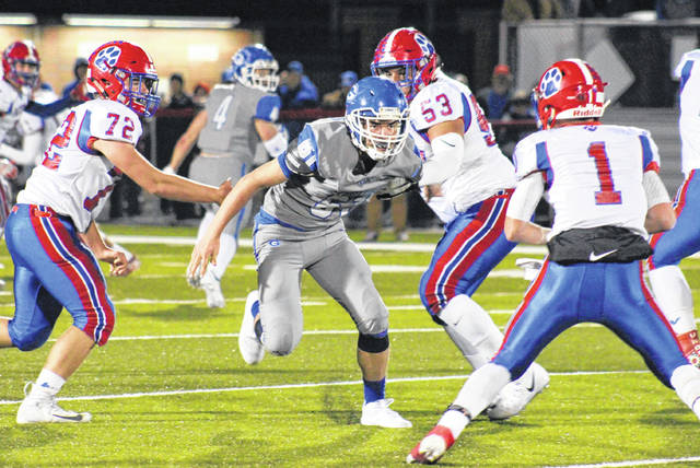 Gallia Academy sophomore Coen Duncan (61) breaks through the Licking Valley line and pressures quarterback Chase Whisner (1), during the Blue Devils 36-12 setback on Saturday in Jackson, Ohio.