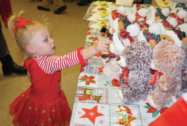 Ornaments, candy canes, cookies, stockings and stuffed animals were all gifts from Santa at the Mason Town Hall following the Christmas parades in the Bend Area. Pictured is a small girl as she tries to make her stuffed animal choice.