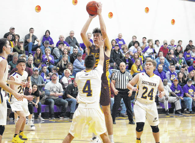 Meigs junior Bobby Musser attempts a high-post shot in between Tornadoes Weston Thorla (4) and Jensen Anderson (24), during the Marauders' 60-43 victory on Friday in Racine, Ohio.