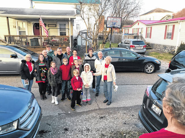"On Christmas Eve, as they've done for many years, members of the First Church of God traveled around Point Pleasant, spreading holiday cheer by singing Christmas songs. Pictured are church members making a stop on 5th Street in Point Pleasant at the home of Jane Bowles. Carolers sang ""Silent Night"" and ended their playlist with ""We Wish You A Merry Christmas."""