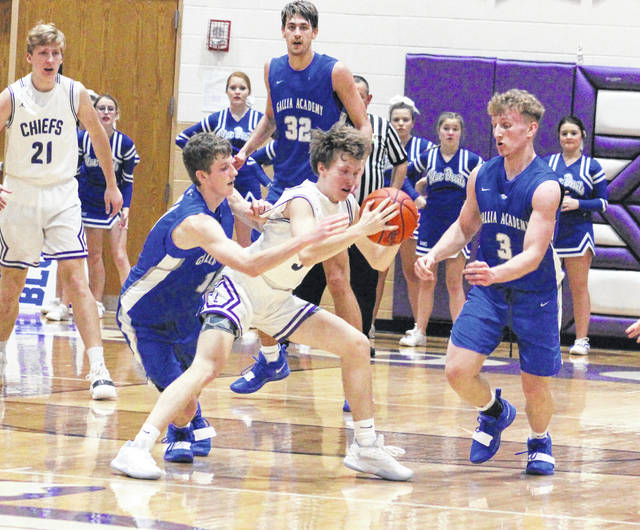 Gallia Academy seniors Blaine Carter and Caleb Henry (3) apply pressure to Logan's Teagan Myers during the first half of Friday night's non-conference boys basketball contest at Jim Myers Gymnasium in Logan, Ohio.