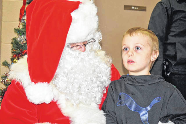 In wide-eyed wonder, six-year-old Landon Smith is pictured as he tells Santa his list of Christmas wishes at the New Haven Fire Station on Saturday. Santa also passed out treat bags to the dozens of children who sat on his lap.