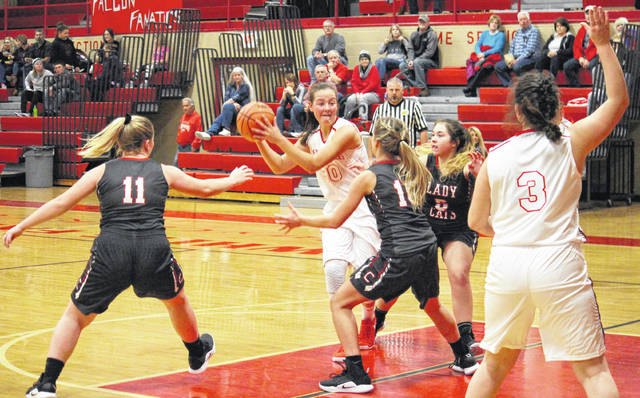 Wahama freshman Lauren Noble (30) passes to sophomore teammate Victoria VanMatre (3), during the Lady Falcons' 48-41 victory on Wednesday in Mason, W.Va.