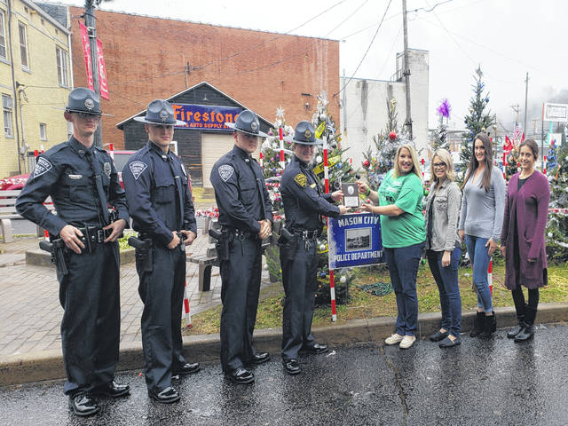 The People's Choice winner for the Light of Christmas tree project is the Mason City Police Department. Those pictured from left to right are Clayton Gibbs, patrolman, Tyler Doss, patrolman, Austen Toler, patrolman, Colton Mckinney, police chief, Brandy Barkey Sweeney, Light of Christmas tree project founder and Mason County Toys for Kids county coordinator, Ashley McGill, Nikki McGrath, and Mariah Toler.