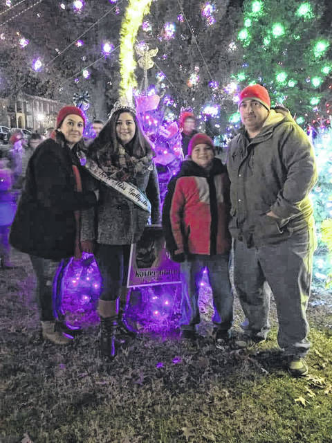"Pictured is the Long family, from left to right, Angie, Kenzie, Josh, and Larry in front of the ""in memory"" tree they decorate each year in memory of Kaylee Long who passed away in 2014."